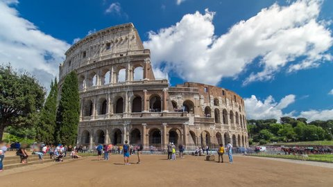 Many tourists visiting The Colosseum or Coliseum timelapse hyperlapse, also known as the Flavian Amphitheatre in Rome, Italy. Cloudy blue sky. Zoom in