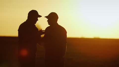 Deal in agribusiness. Two male farmer communicate on the field, use a tablet - shake hands. Silhouettes at sunset