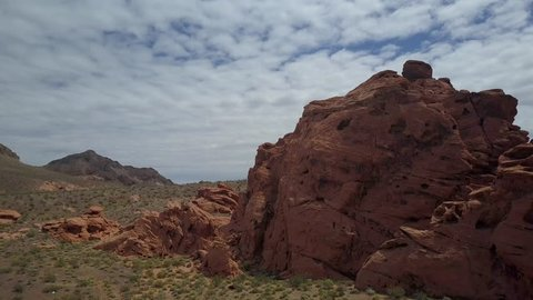 Aerial fly to red rock desert near Valley of Fire Nevada pull back. Public recreation and nature preservation area. Scenic desert landscape mountains. Natural ecological tourist tourism destination.