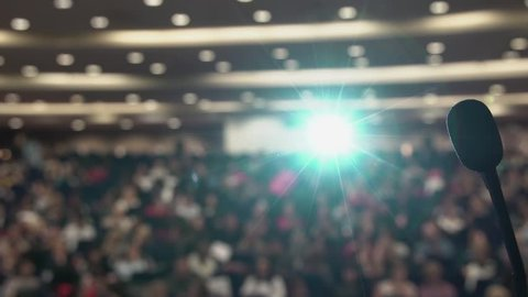 Many people sit in large hall at conference. Projector light via the microphone.