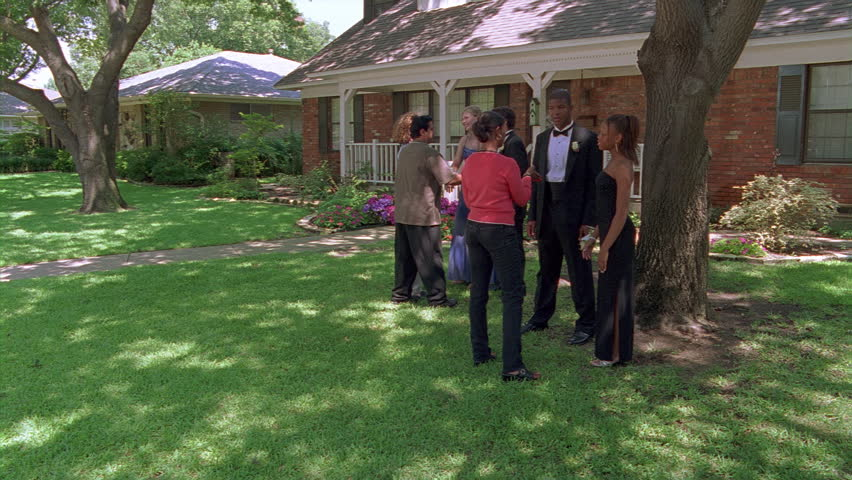Parents admiring two teenage couples in prom clothes on lawn of suburban house