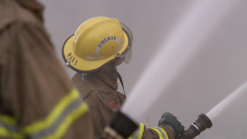 Fireman spraying water from a hose   Shutterstock HD Video #26582873