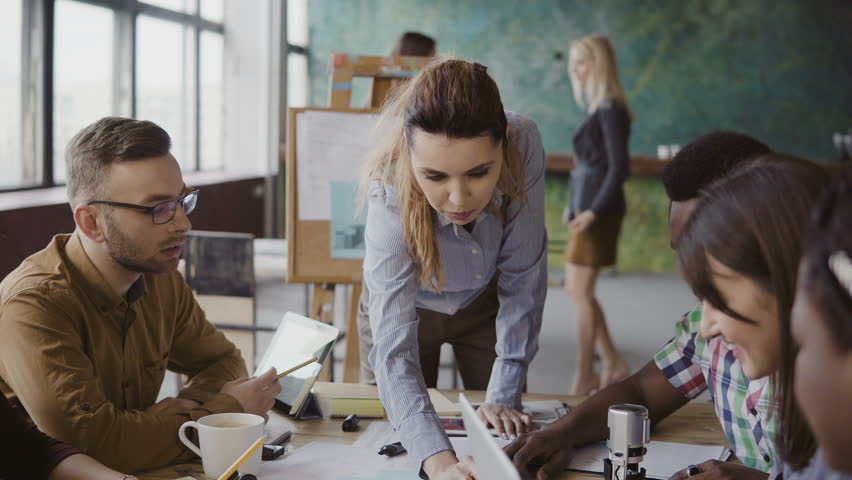Female team leader standing near table and giving direction to young creative team. Brainstorming of multiethnic group. | Shutterstock Video #26591243