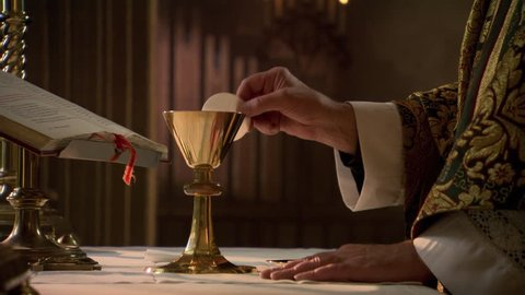 Hands of priest with wafer and chalice during Eucharist