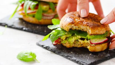 Delicious vegan burger with avocado, fresh vegetables, herbs and olive oil.