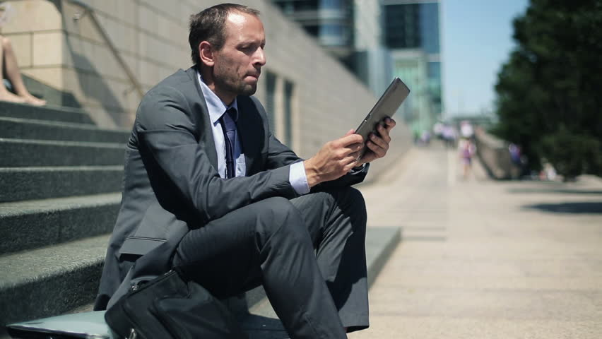 Businessman reading news on tablet computer in the city