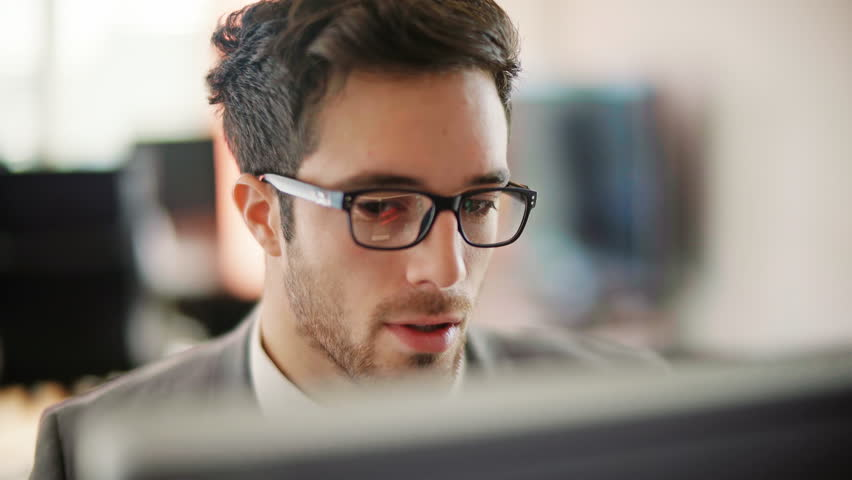 Handsome young man working in a touchscreen computer or tablet. Businessman with glasses in an office space. Technology. Daylight. Dolly shot.  | Shutterstock HD Video #26621023
