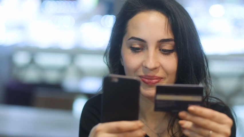 Frontal closeup of smiling young elegant attractive girl with deep brown eyes in black dress trying to buy something enjoyable with her smartphone and plastic cardshopping Steadicam slow motion shot