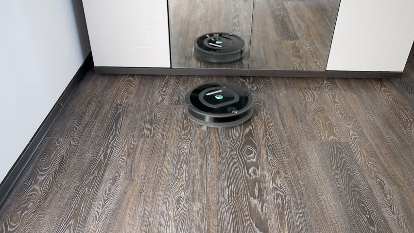 The robot vacuum cleaner removes the floor covered with a laminate, rotating in a spiral and in an arbitrary route | Shutterstock HD Video #26657683