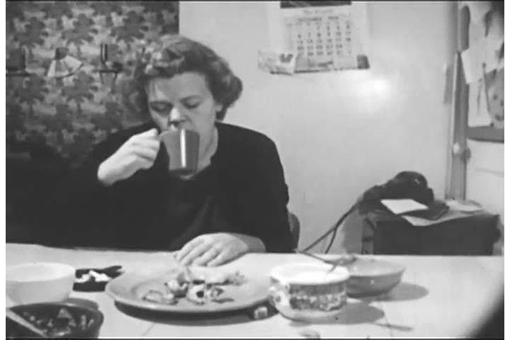 1950s: A female addict is too groggy to prevent her son from burning himself in their kitchen, in 1955.