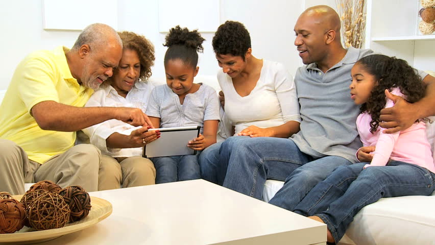 Three generations African American family using wireless tablet home entertainment