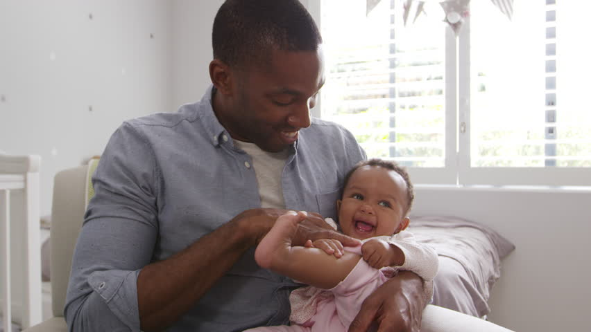 Father Sitting In Nursery Chair Holding Baby Daughter