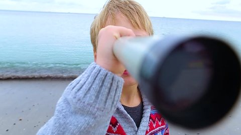 Little child looks through old telescope at something interesting in blue sea. Happy 8 year old kid has fun on beach on vacation in cool spring or autumn season. Real time hd video footage