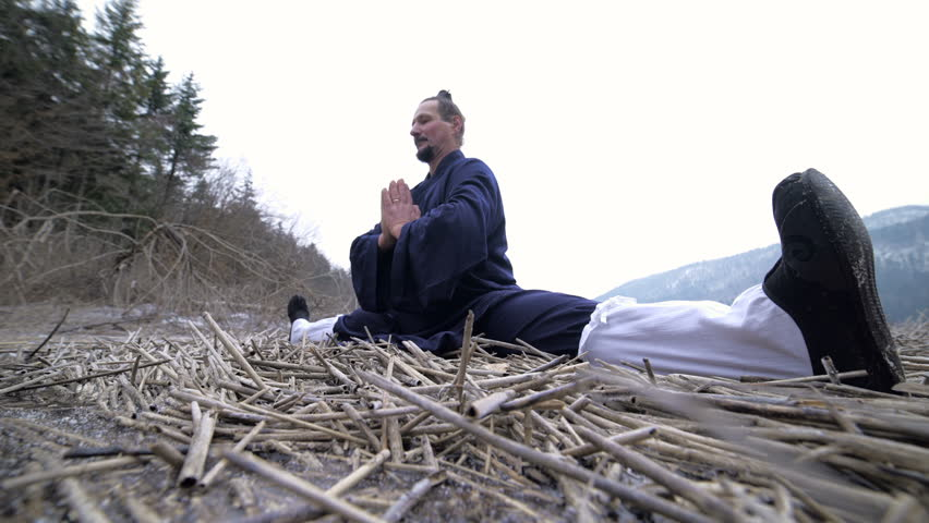 Kung Fu Master Training Sitting Leg Stretch 4K. Low angle dolly slide of man in traditional kimono in focus sitting on ground outside.