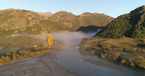 Aerial footage in Wanaka, New Zealand, in autumn. The blanket of clouds rush out over the river.
