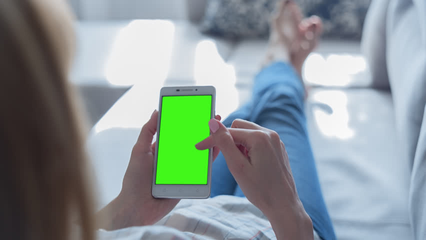 Young Woman laying on a couch uses SmartPhone with pre-keyed green screen. Few types of motion - scrolling up and down, tapping, zoom in and out. Perfect for screen compositing. Made from 14bit RAW   Shutterstock HD Video #26729263