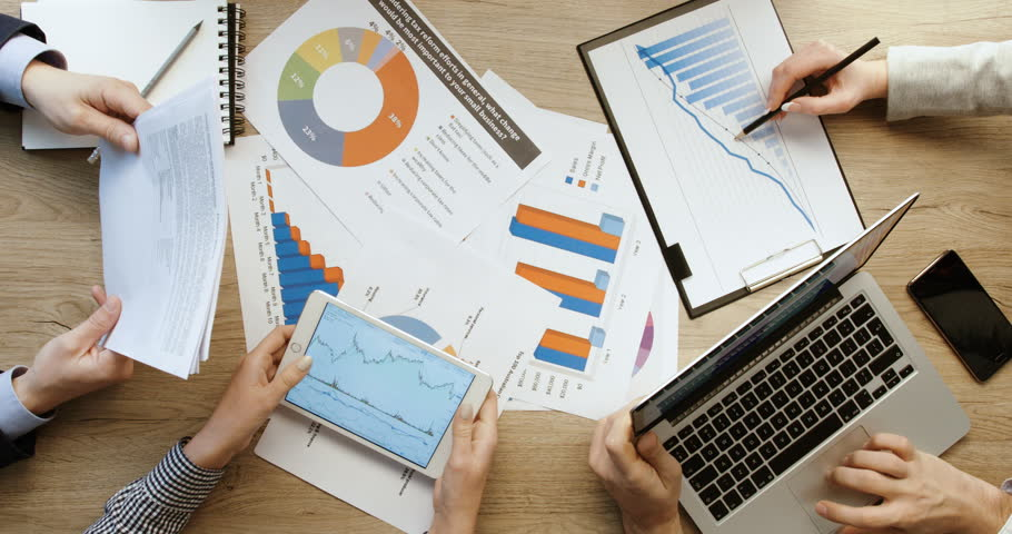 Top view of hands. Business team checking financial charts and graphs, pointing and working with tablet and laptop, writing in notebook at office wooden desk. Quick motion. Time lapse | Shutterstock HD Video #26737099