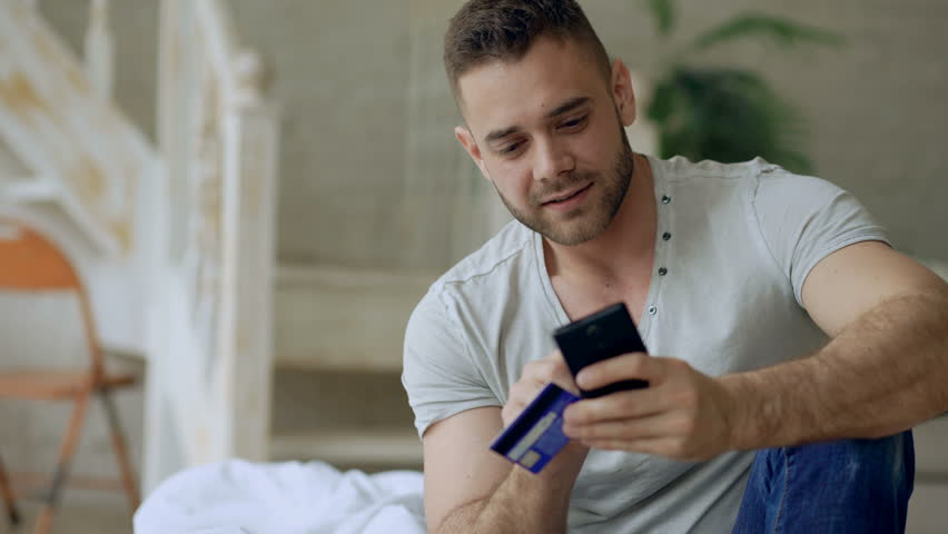 Attractive young man with smartphone and credit card shopping on the internet sit on bed at home | Shutterstock HD Video #26741488