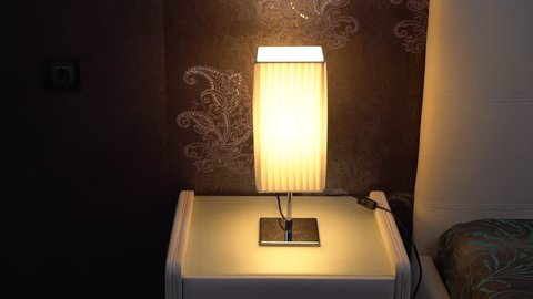 A Man S Hand Turns On Table Light On A Bedside Table Near The Bed Early Morning