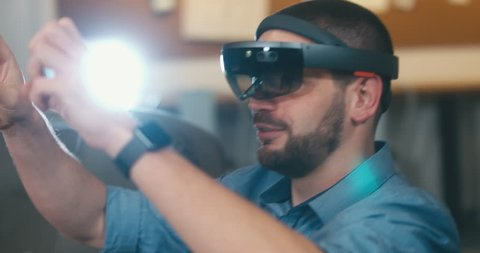 CU young adult Caucasian male using holographic augmented reality glasses in trendy office. Future concept. 4K UHD RAW edited footage