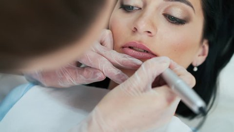 Cosmetologist applying permanent makeup on lips. Permanent make up.