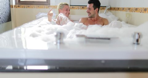 Young Couple In Bath Together Drink Champagne Talking, Man And Woman Lover Enjoy Spa At Home Slow Motion 60