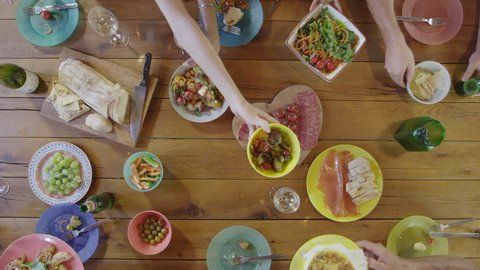 Friends passing food around a dinner table, overhead, shot on R3D