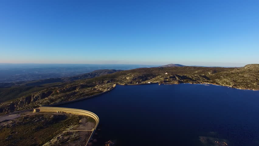 Aerial of a dam, flying sideways, little white House on the peak of some rocks, car driving on the road, located in Serra da Estrella, Portugal, beautiful blue water and cloudless sky, 4K Drone