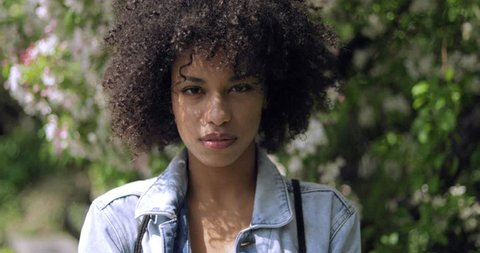 Young gorgeous black woman with short curls in denim jacket looking at camera on background of blooming trees in park.