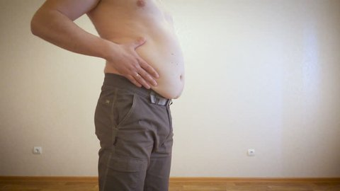 A man is posing showing a fat stomach. Fat man massages his belly.