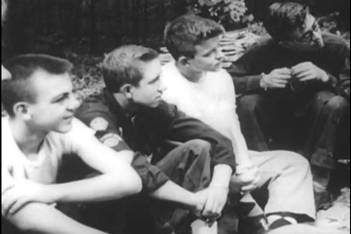 1950s: An adolescent boy camps with friends and meets with a religious advisor and his sister sings in a church before kneeling to pray, in 1955.