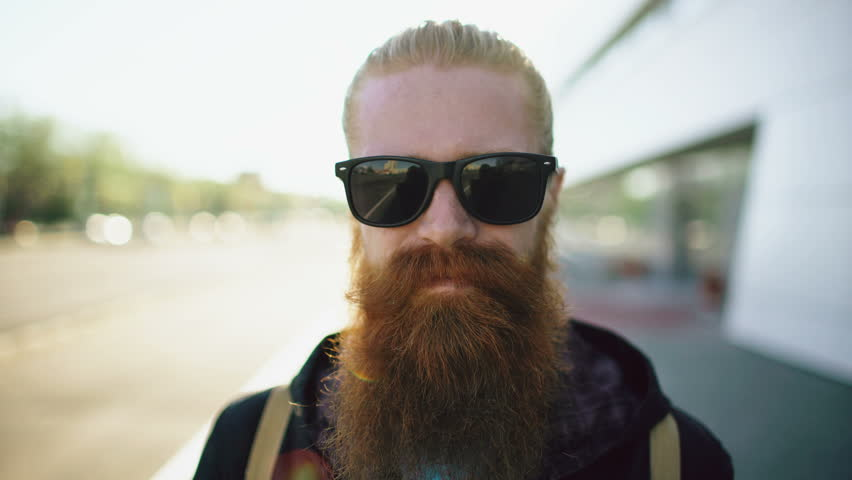 Closeup portrait of young bearded hipster man in sunglasses smiling and posing while travelling city street | Shutterstock HD Video #26867548