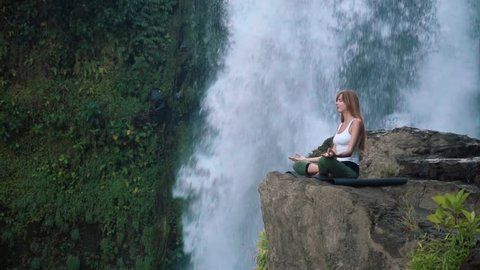 Young woman practicing yoga lotus pose next to Tegenungan Waterfall, Ubud