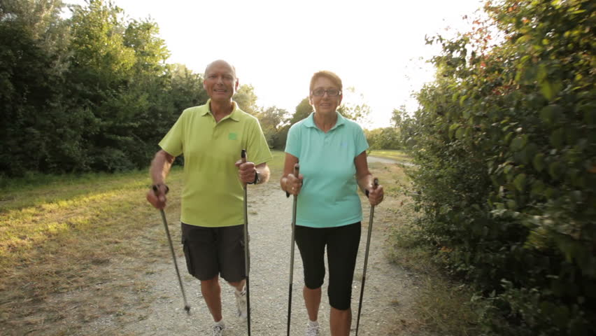 tracking shot happy smiling retirees nordic walking in late afternoon