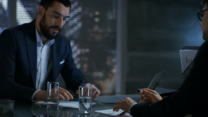 Late at Night Businessman Businessman Has Conversation with Important Client, They Come to an Agreement, Sign Contract and Shake Hands. In the Background Big City Window View. Shot on RED EPIC-W 8K.
