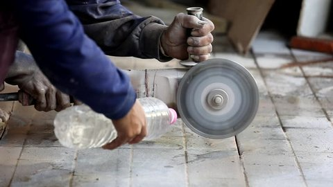 Worker using concrete cutting machine to cut hard floor, they pour water to reduce dust and noise