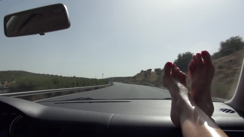 woman feet barefoot on car dashboard driving on a highway in Spain