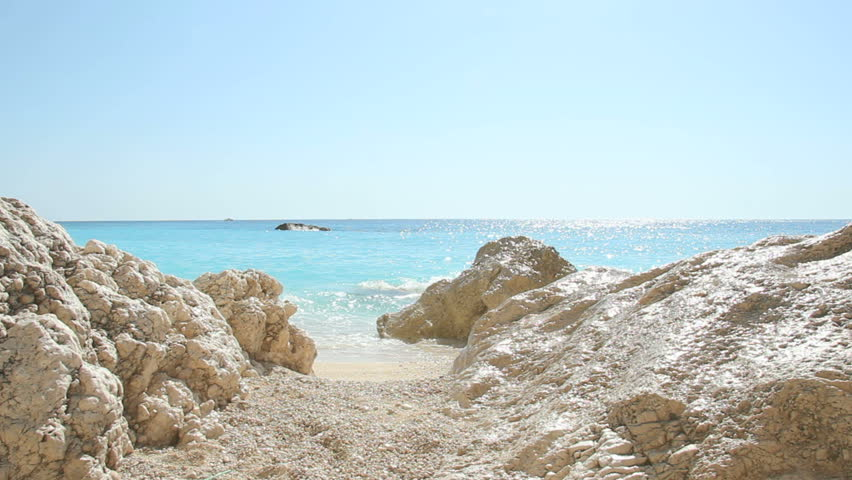 Waves splashing on rocks - Beautiful turquoise waves splashing on large rocks on a white sandy beach, shot on Porto Katsiki Beach, Island of Lefkada, Greece