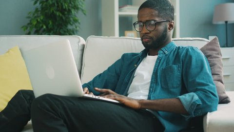 Attractive african man in glasses sitting on the sofa using laptop at home on living background for chatting with friends. Indoor.