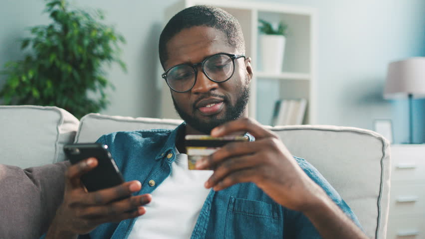 Young african man sitting on the couch, using smart phone for online shopping with credit card on living backround. Indoor. | Shutterstock HD Video #26912593