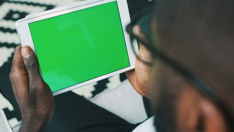 Top view of attractive young african man with glasses using white digital tablet with green screen. Chroma key.