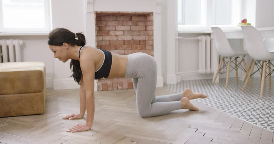 Side view of young fit female in sportive clothing standing on floor of living room on all fours and practicing exercise with pushing leg up. | Shutterstock HD Video #26927263
