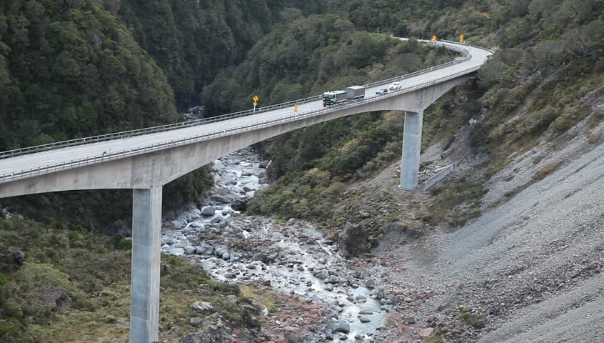 Vehicles, truck and cars drive slow over long bridge across canyon in New Zealand