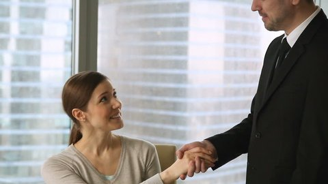 Friendly male boss welcoming young new female employee with handshake at workplace, nice to meet you, congratulating with impressive achievements, thanking for good work result, promoting subordinate