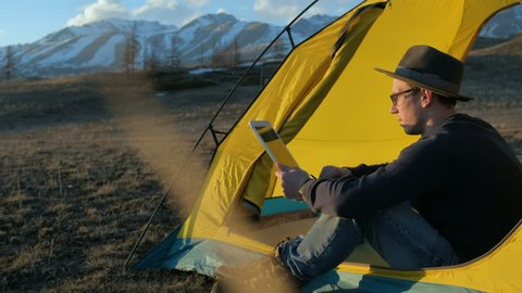 Handsome young man tourist using cell phone and portable mini speaker in touristic tent 20s 4k
