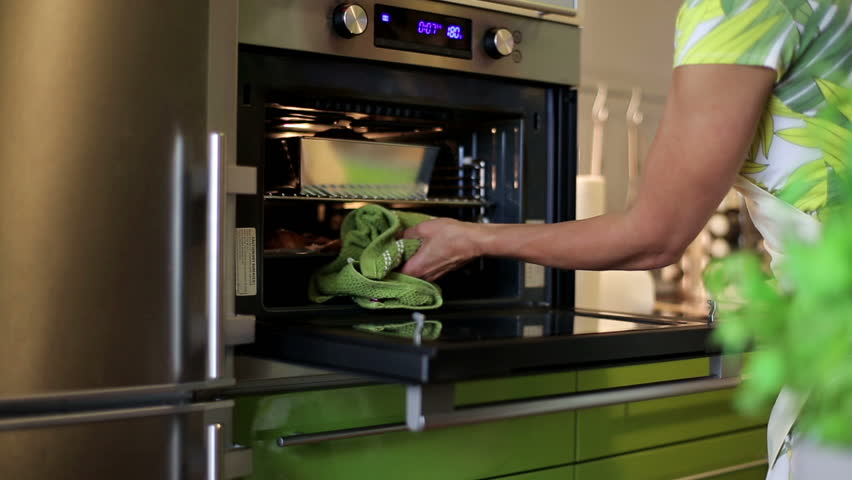Charming woman checking how her cake is doing in the oven