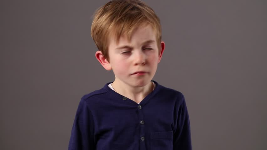 free little 6-year old boy shaking his head and swinging his arms to express his refusal, boredom or happy disagreement, grey background studio