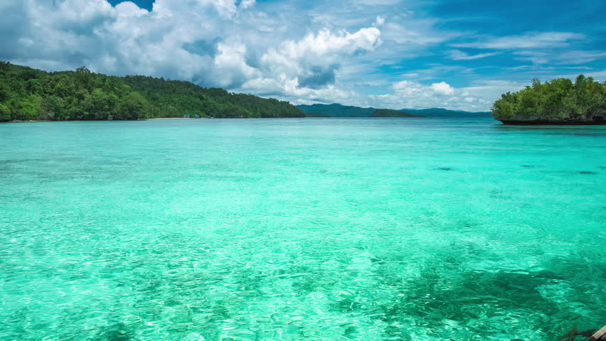 Beautiful blue lagoon with pure clear water and rainy clouds in background, Gam Island, West Papua, Raja Ampat, Indonesia