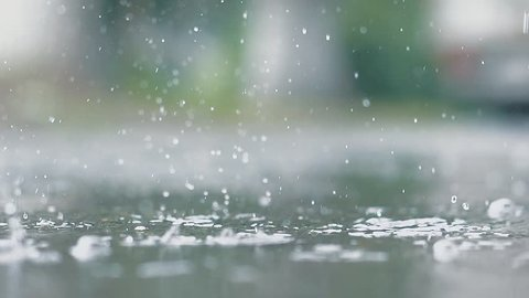 It is raining outside. Rain drops break in puddle. Slow motion. Close up.