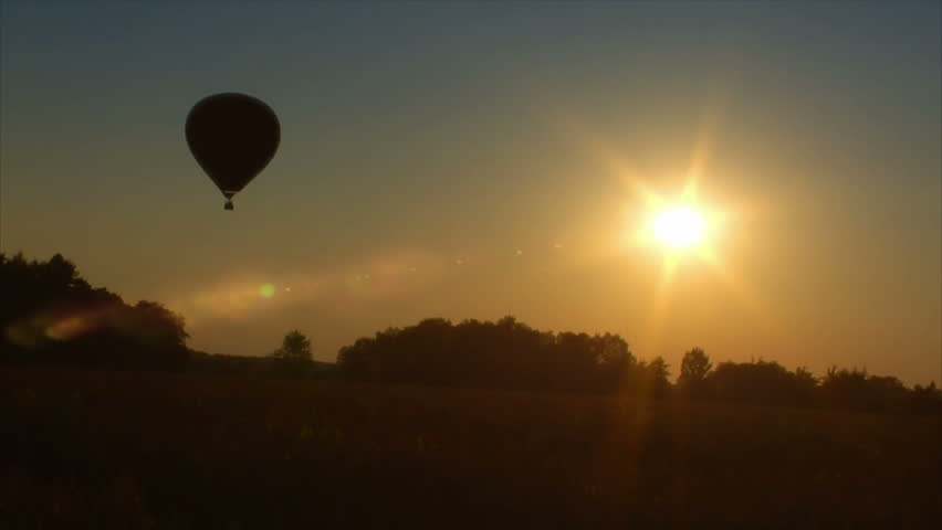 A hot air balloon lift off in sunrise / sundown.